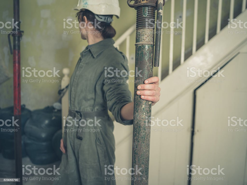 Woman in hard hat inspecting acro props stock photo