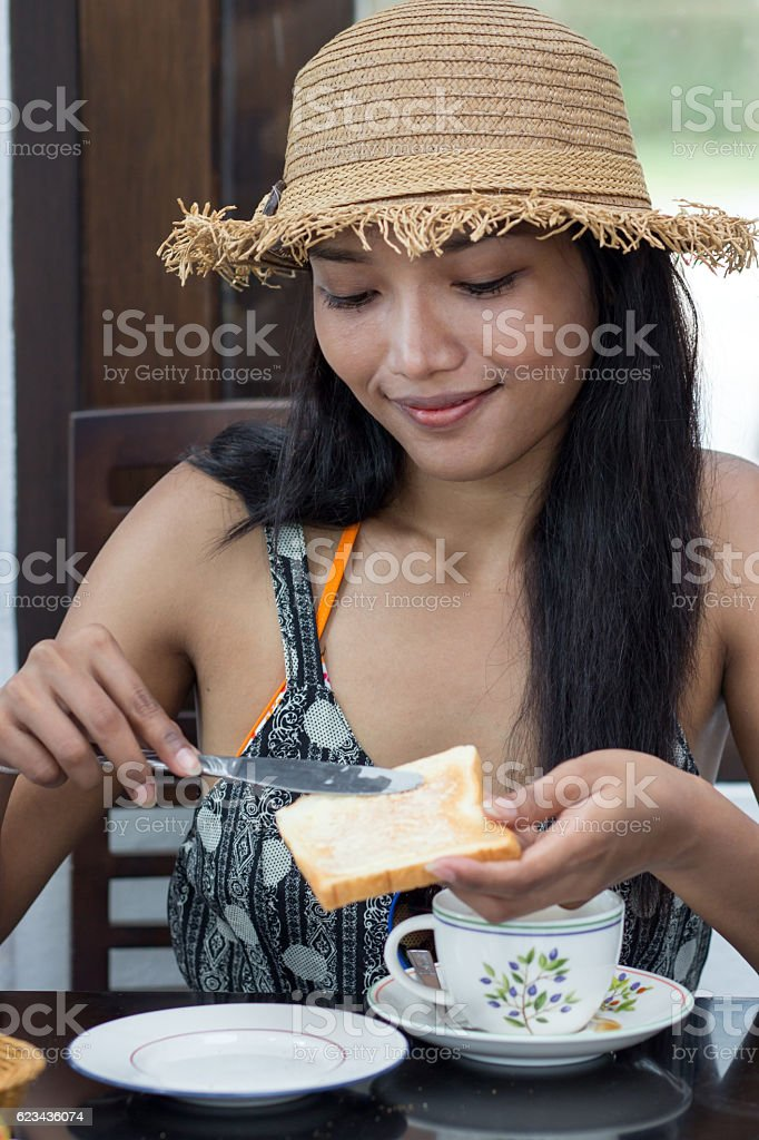 Woman in hat a greased toast with jam stock photo