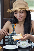 Woman in hat a greased toast with jam