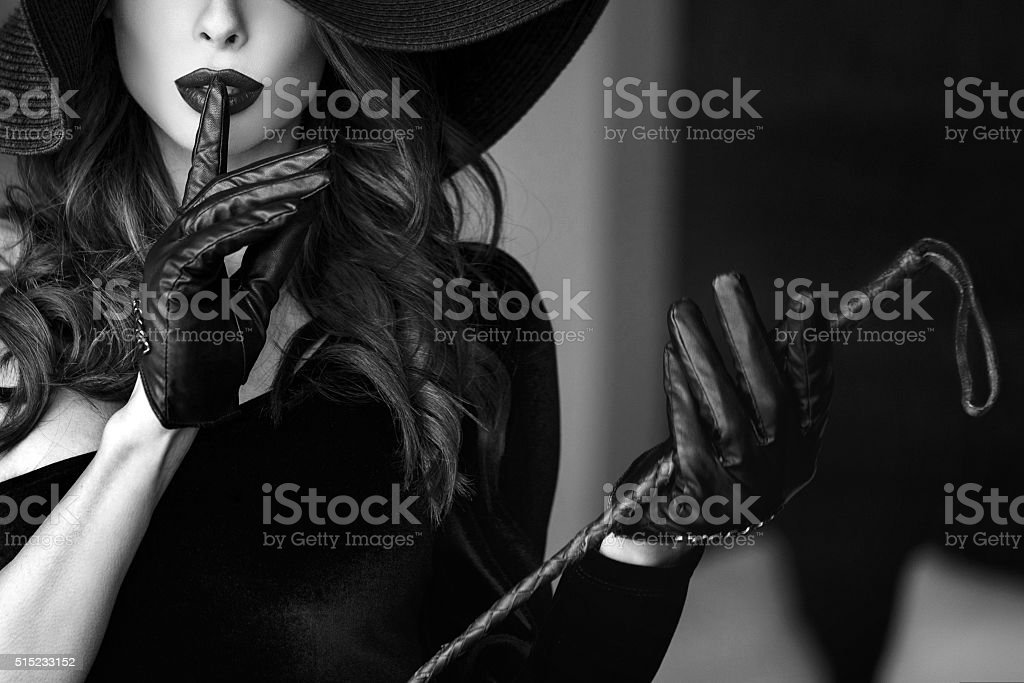 Woman in hat and whip showing no talk stock photo