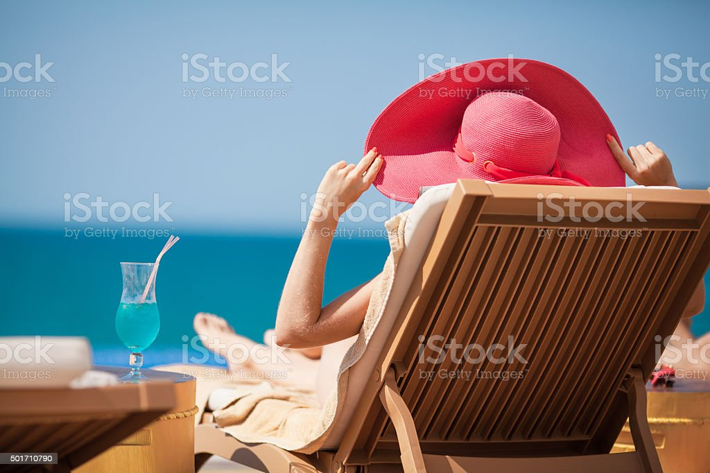Woman in hat on a sun lounger near the sea stock photo