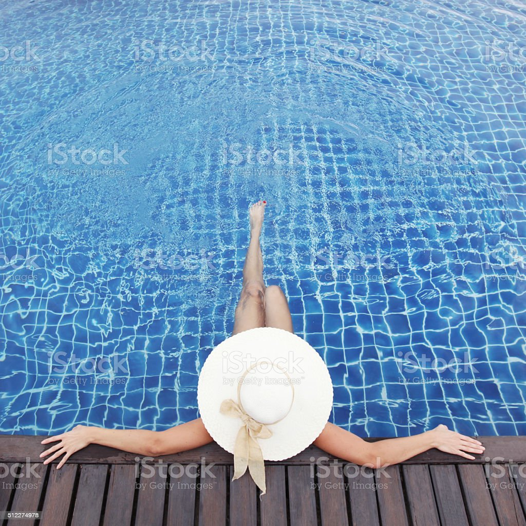 Woman in hat relaxing at pool stock photo
