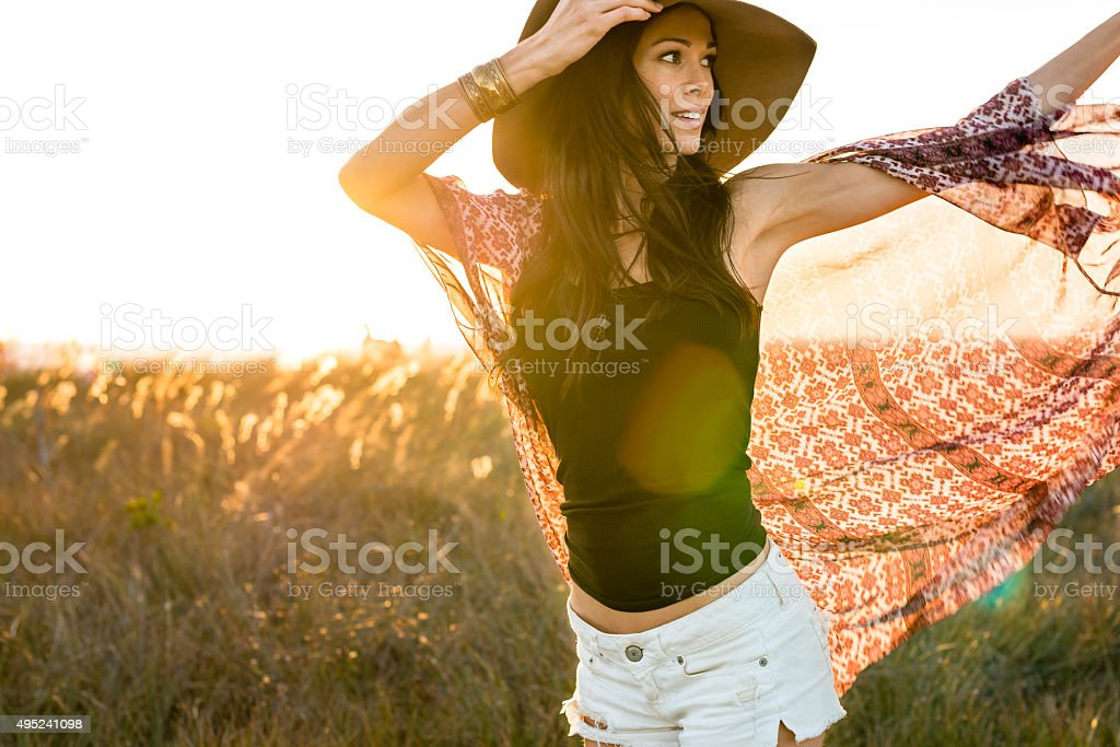 Woman in hat running through field stock photo