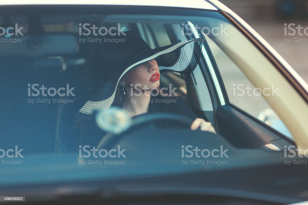 Woman in hat sitting behind the wheel of a car. stock photo