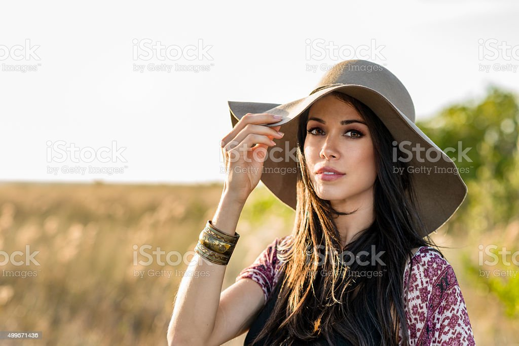 Woman in hat standing in field stock photo