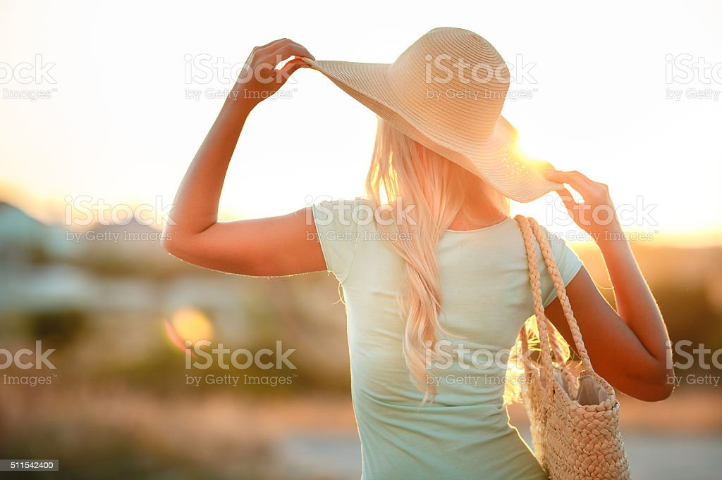Woman in hat with large fields, at sunset stock photo