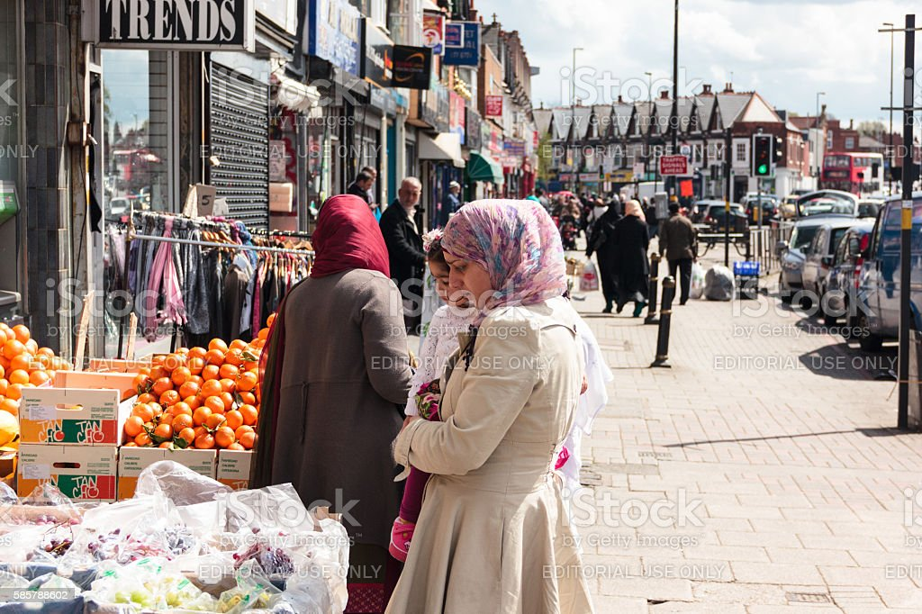 Woman in head scarf shopping while holding child stock photo