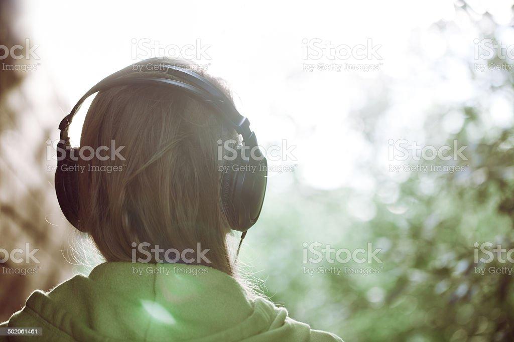 Woman in headphones against bright sunlight stock photo