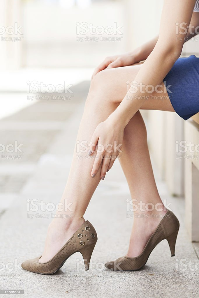 Woman in heels massaging tired legs royalty-free stock photo
