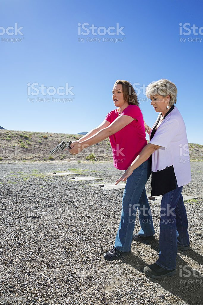 Woman in her 30s getting a gun safety lesson royalty-free stock photo