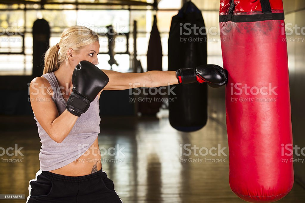 Woman in her 40s hitting punching bag stock photo