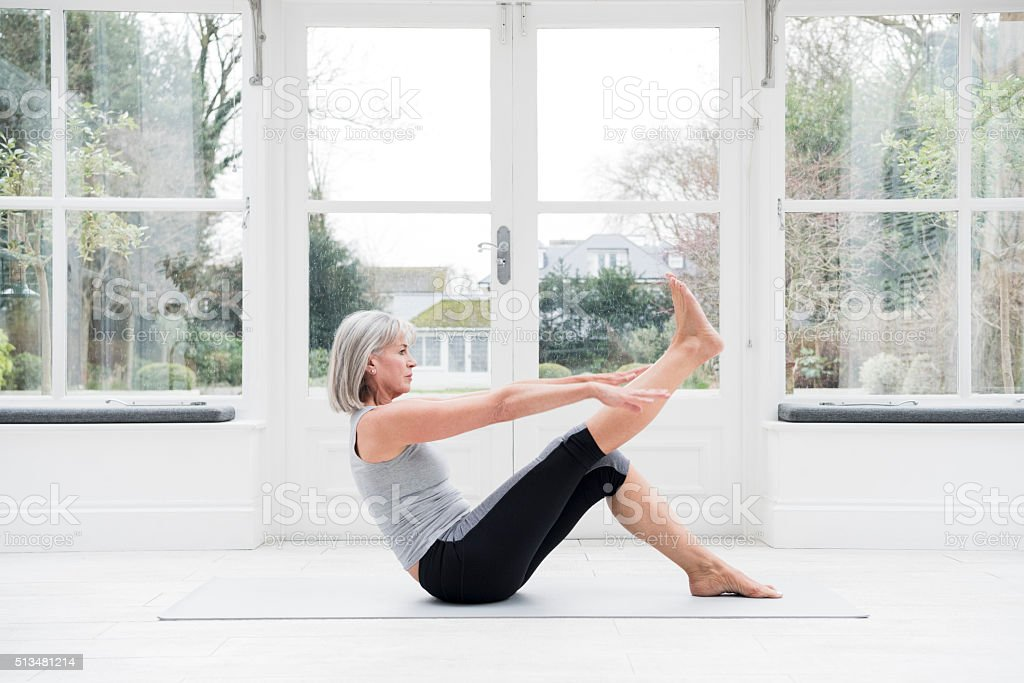 Woman in her 60s stretching leg at home stock photo