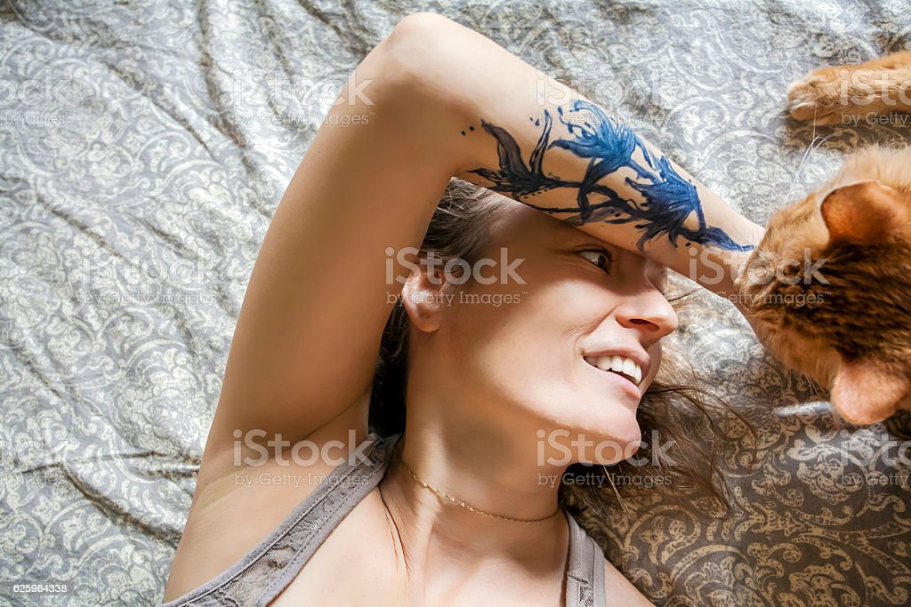 Woman in her bed with her beloved cat stock photo