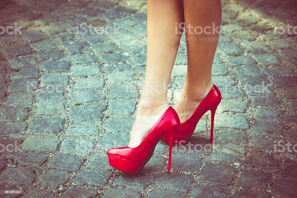 Woman in high heel shoes on an uneven stone path stock photo