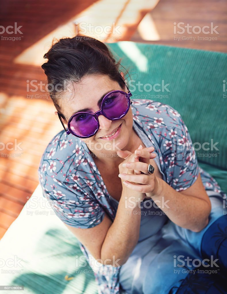 Woman in hippie purple sunglasses smiling happily stock photo