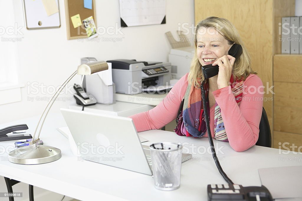 Woman in home office on telephone royalty-free stock photo