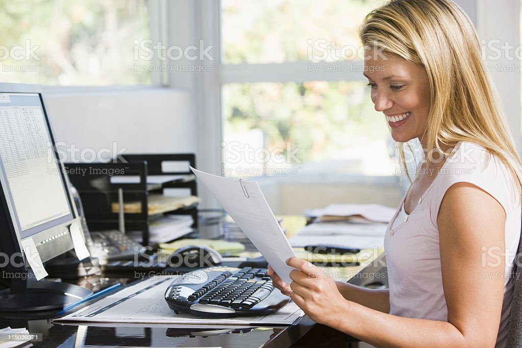 Woman in home office with computer and paperwork royalty-free stock photo