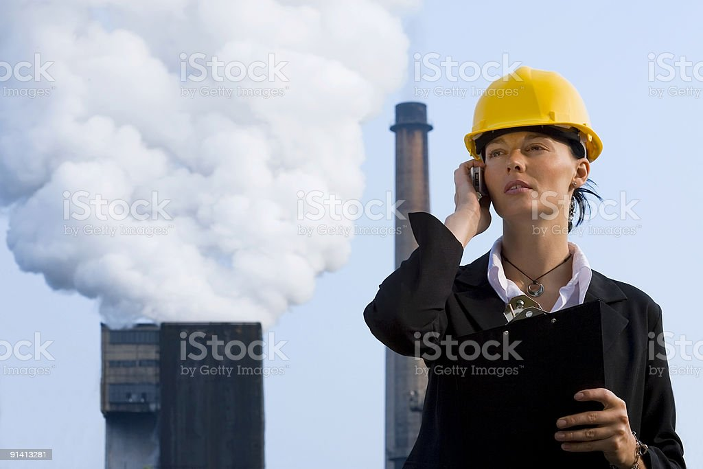 Woman In Industry Wearing Hard Hat Talking on Cell Phone stock photo