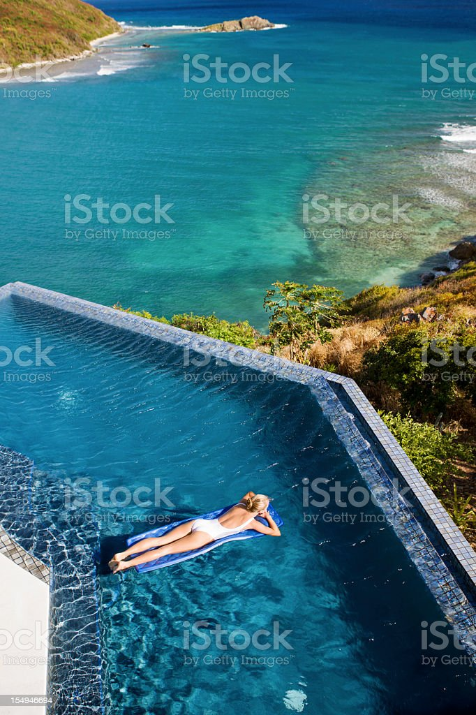 woman in infinity pool floating on a raft royalty-free stock photo