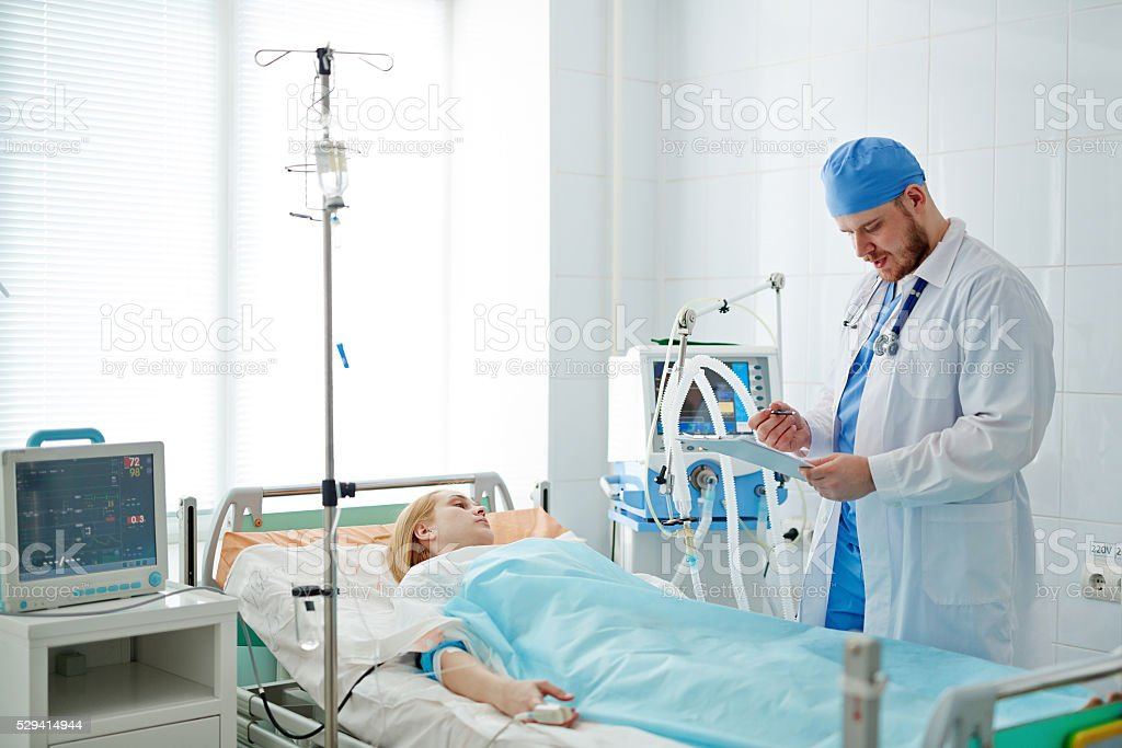 Doctor standing at bed with patient in intensive care