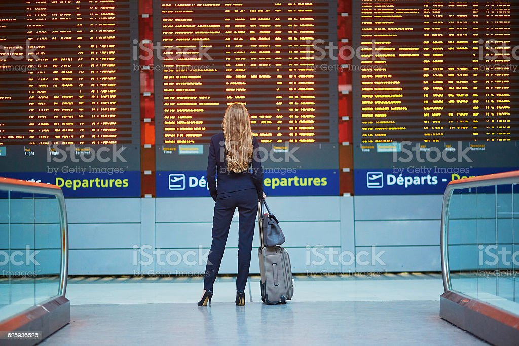 Woman in international airport looking at the flight information board stock photo
