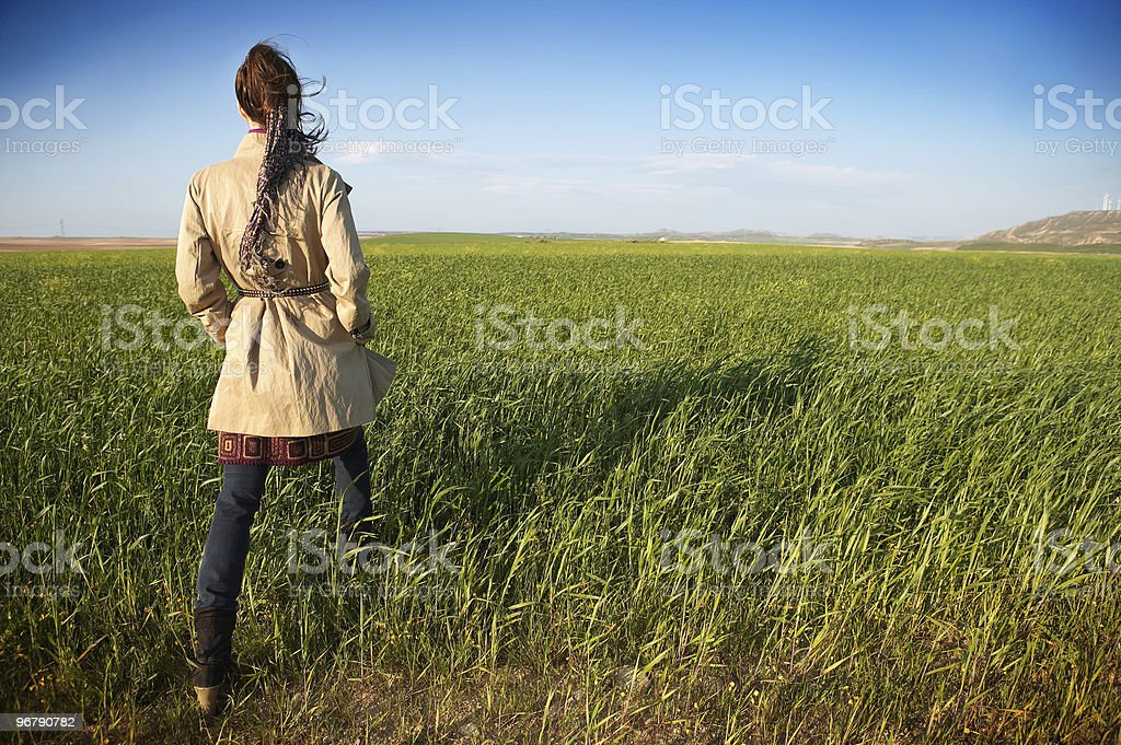 Woman in jacket walking through green field royalty-free stock photo
