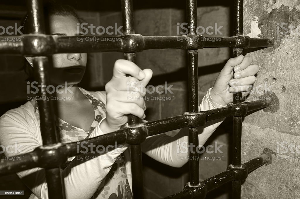Woman in jail holding onto metal bars royalty-free stock photo