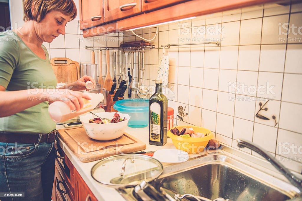 Woman in Jeans Adding Wine Vinegar to Radicchio, Home, Europe stock photo