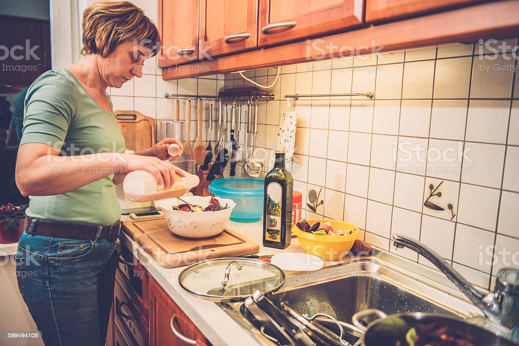 Woman in Jeans Adding Wine Vinegar to Radicchio, Home, Europe stock photo