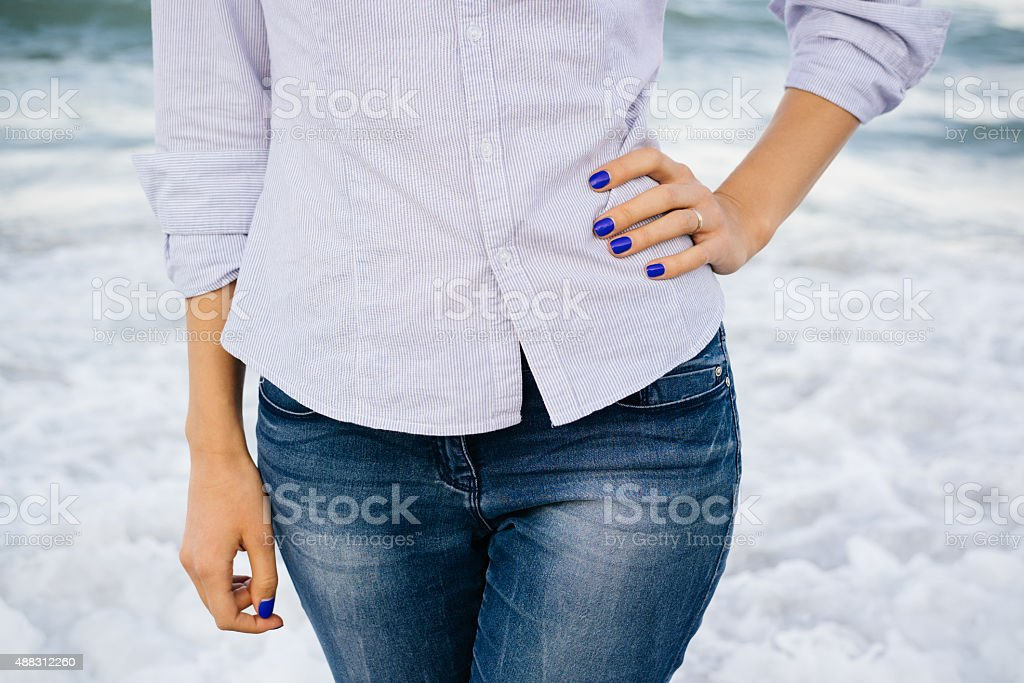 Woman in jeans and shirt standing in the sea foam stock photo