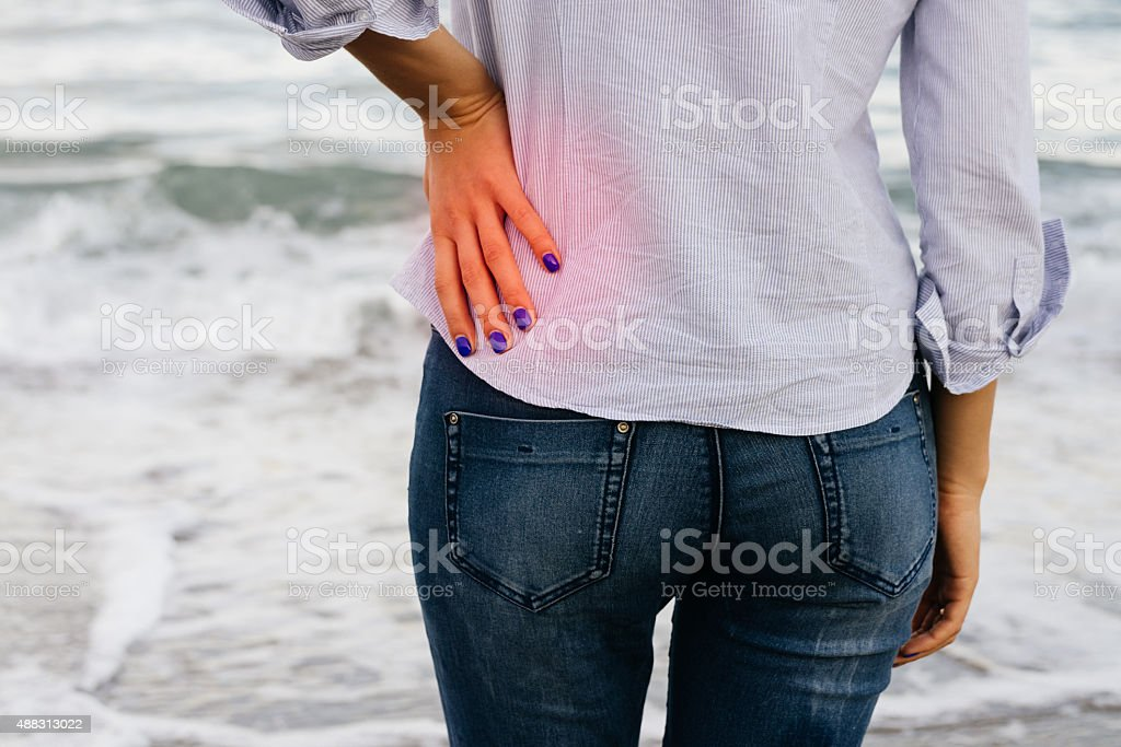 Woman in jeans and shirt standing on the shore stock photo