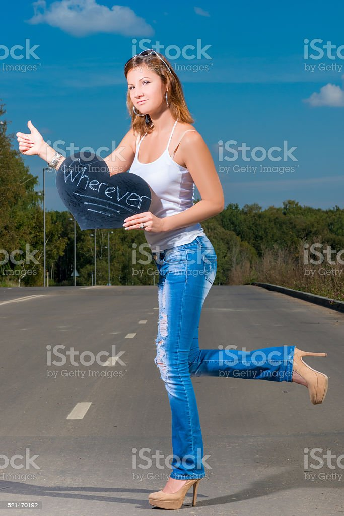 woman in jeans and t-shirt travels hitchhiking stock photo
