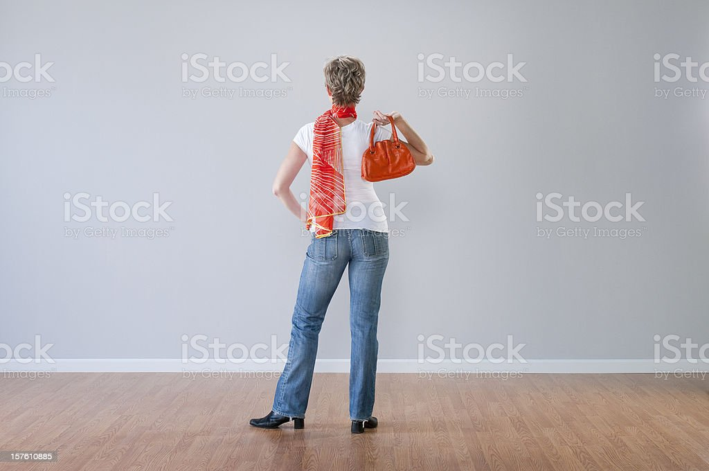 Woman In Jeans Looking At Blank Wall royalty-free stock photo