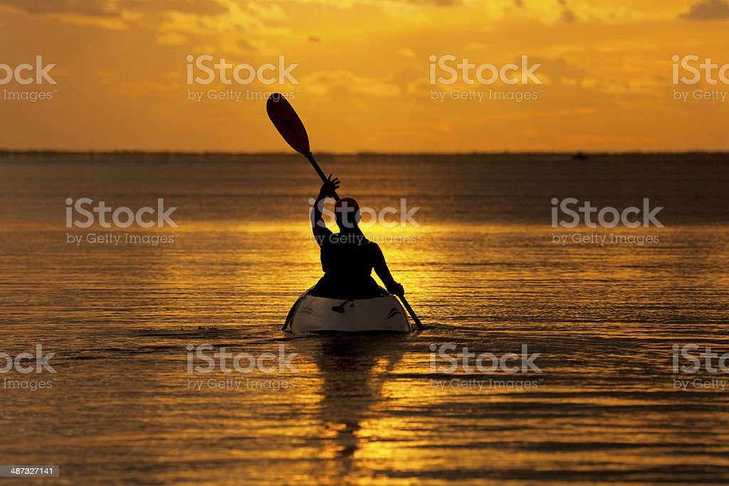 woman in kayak enjoying golden Florida sunset stock photo