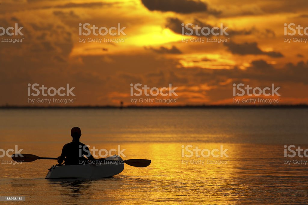 woman in kayak enjoying golden sunset stock photo