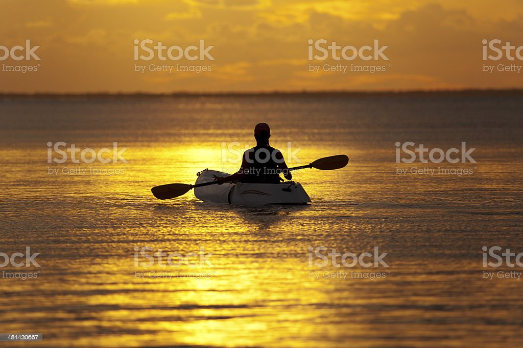woman in kayak enjoying golden sunset while rowing stock photo