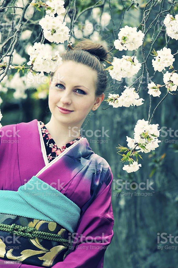 Woman in kimono against sakura royalty-free stock photo