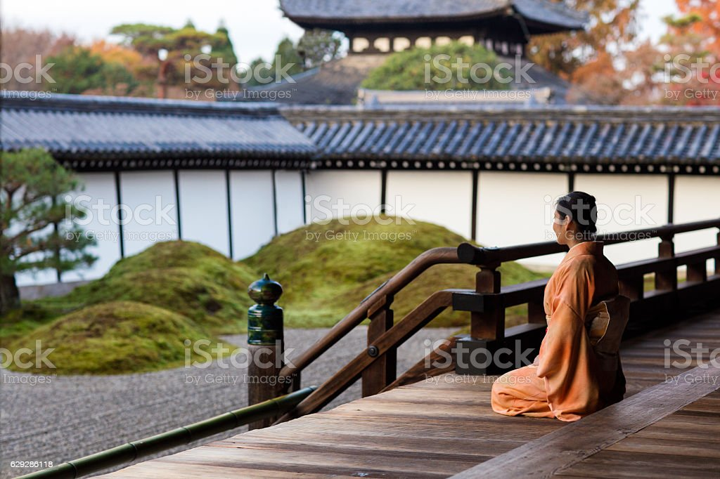 Woman in kimono kneeling at a Japanese temple stock photo