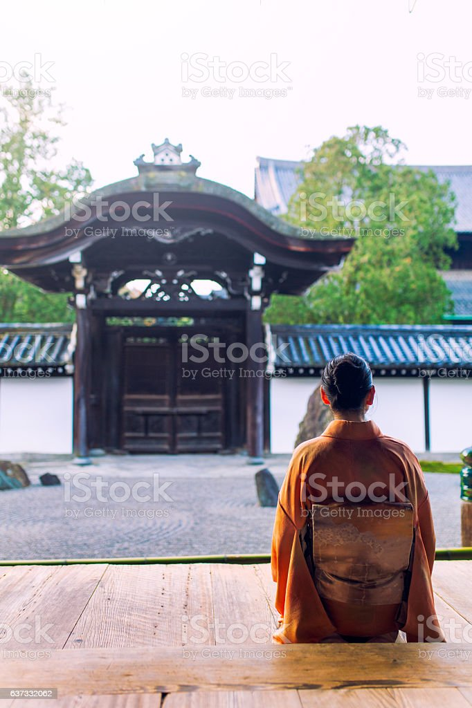 Woman in kimono kneeling at temple in early morning stock photo