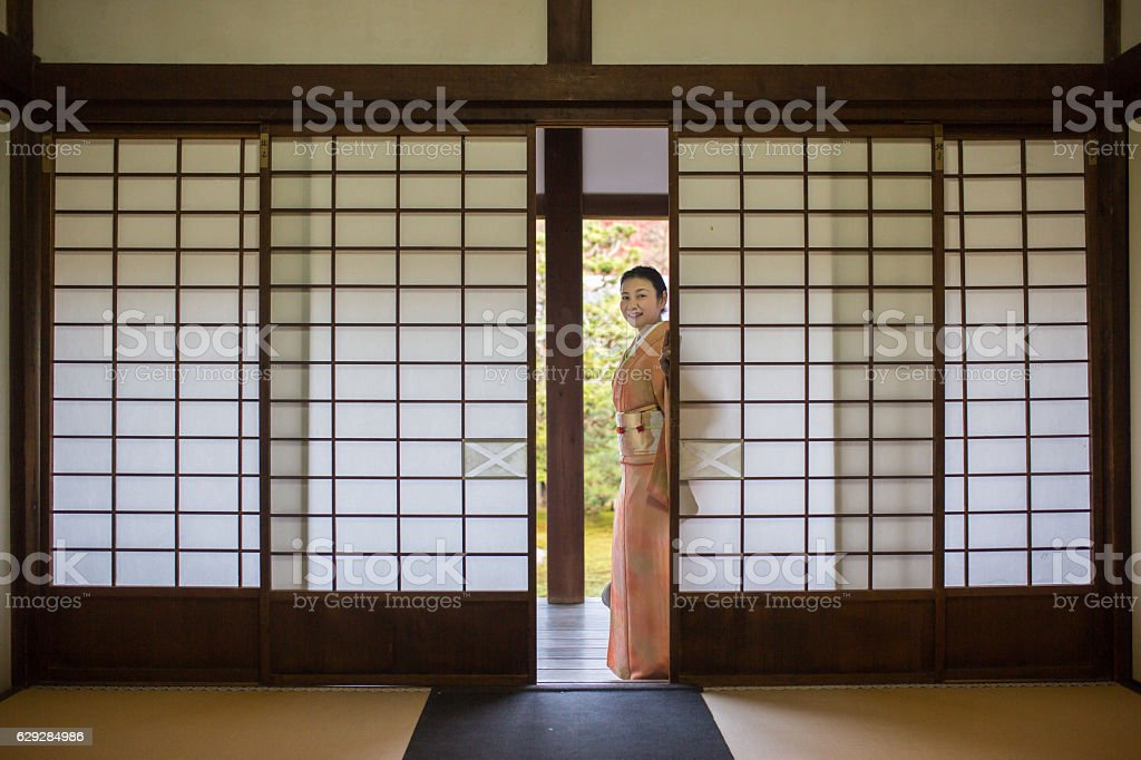 Woman in kimono looking through sliding doors in a temple stock photo