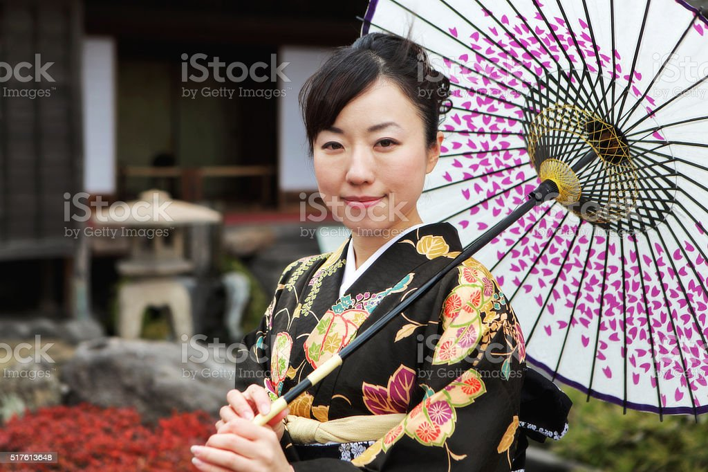 Woman in kimono with umbrella against traditional Japanese house stock photo