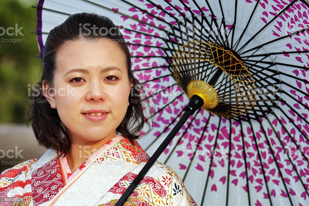 Woman in kimono with umbrella looking at camera stock photo