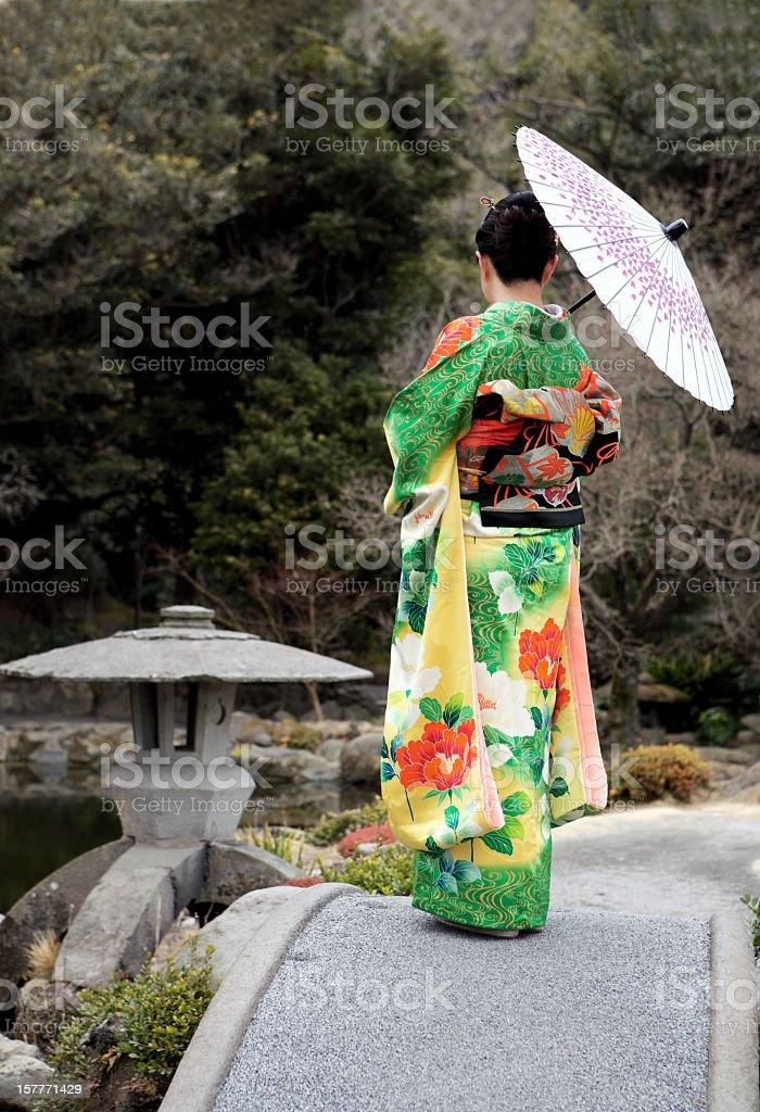 Frau in kimono mit Regenschirm auf der Brücke Lizenzfreies stock-foto