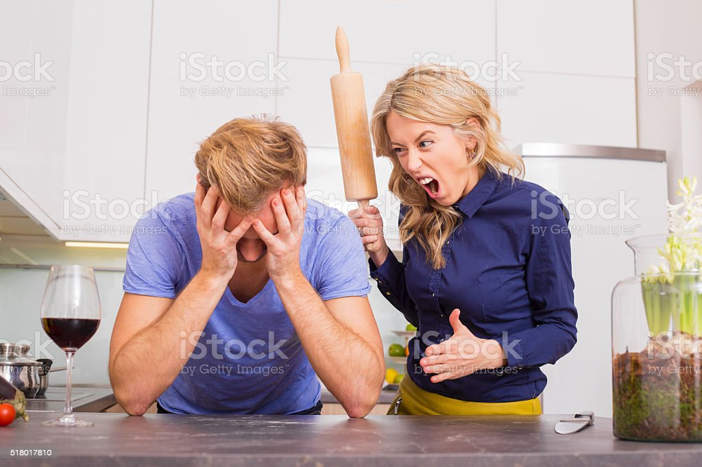 Woman in kitchen being angry at her man stock photo