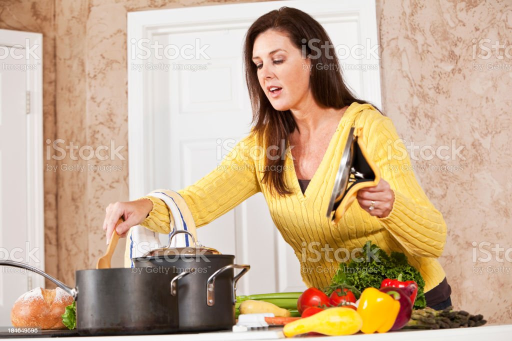 Woman in kitchen cooking on stove royalty-free stock photo
