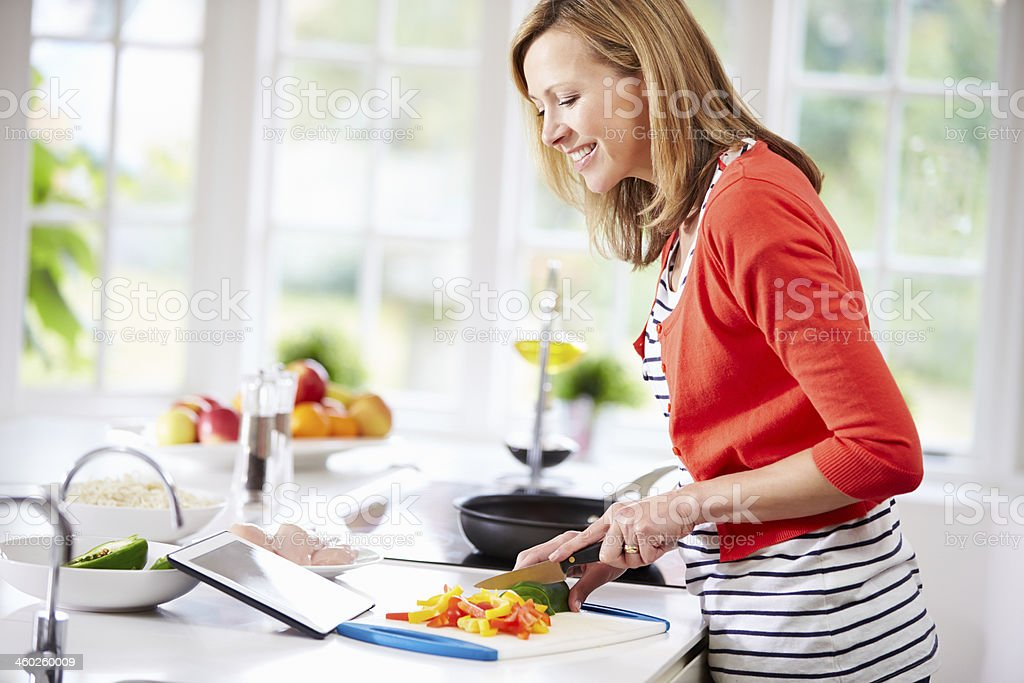 Woman In Kitchen Following Recipe On Digital Tablet stock photo