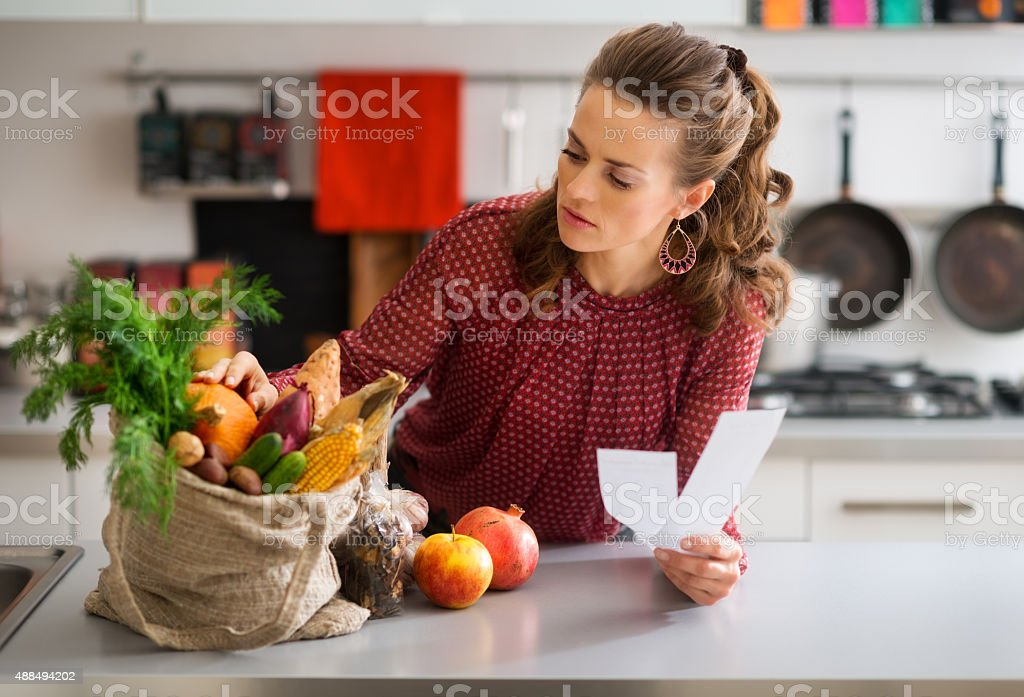 Woman in kitchen holding shopping list looking through items stock photo