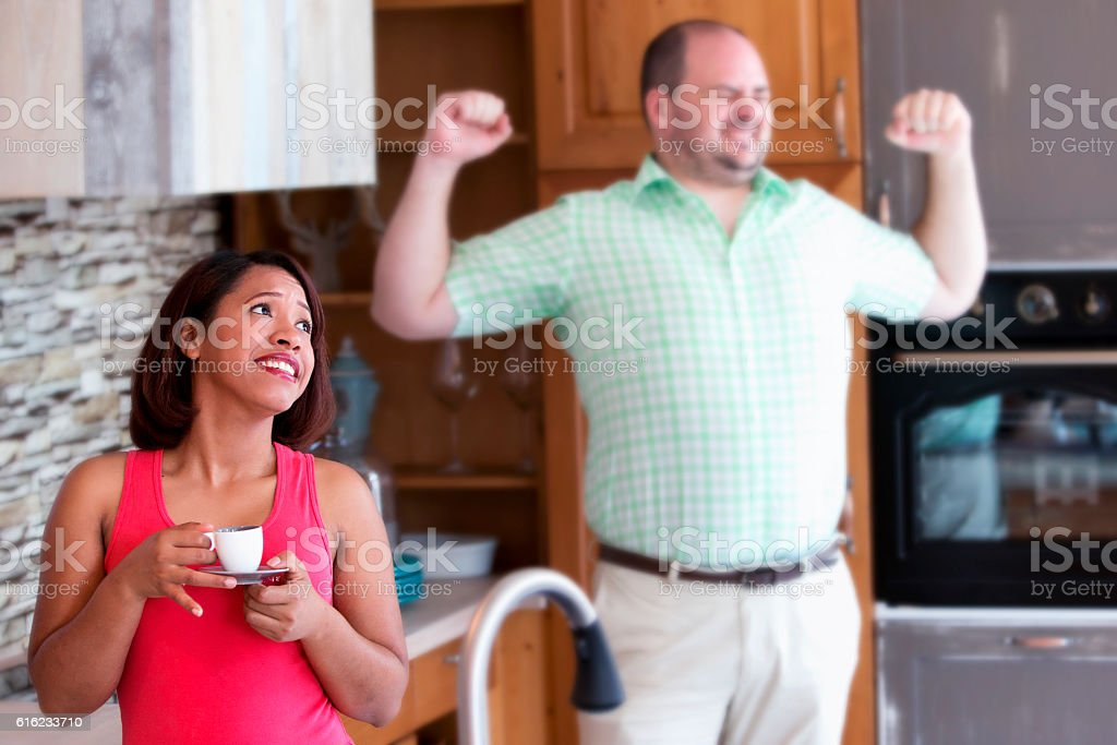 woman  in kitchen looking annoyed while man is yawning stock photo