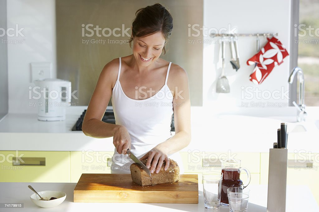 Woman in kitchen slicing bread stock photo