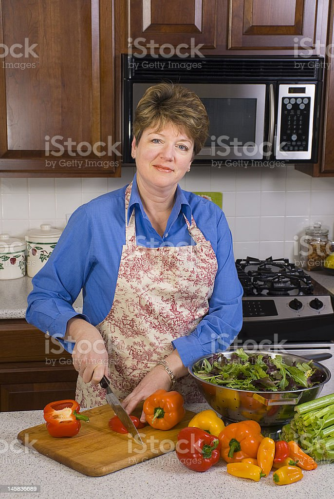 Woman in Kitchen Slicing Peppers royalty-free stock photo